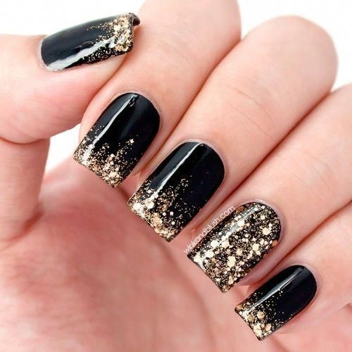 Photo of black nails with dipped gold glitter at tips